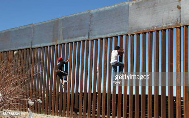TOPSHOT Boys play around climbing the border division between Mexico and the US in Ciudad Juarez Mexico on January 26 2017 US President Donald Trump...