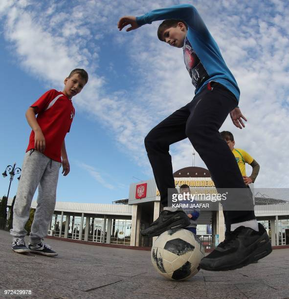 Boys play football in front of the Akhmat Arena stadium in Grozny on June 12 ahead of the Russia 2018 World Cup