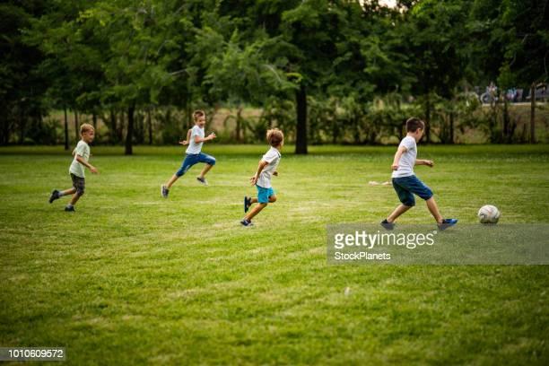 garçons jouent au football dans le parc - club football photos et images de collection