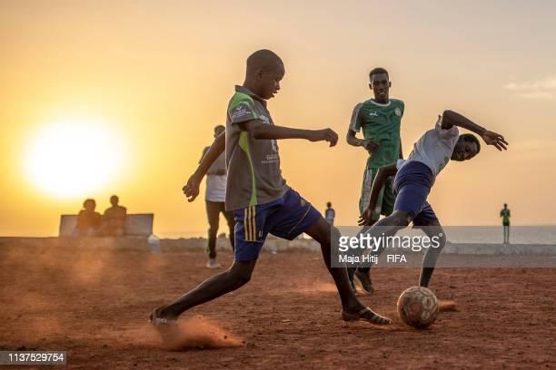 Boys play football near the beach on January 16 2019 in Dakar Senegal