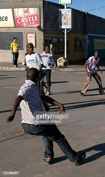 Boys play football on a street of Gugulethu township 20kms from Cape Town on June 22 2010 South Africa's Bafana Bafana football team is playing...