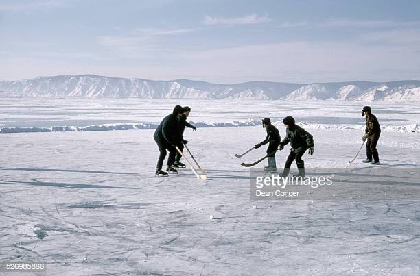 Boys play hockey on a frozen part of Lake Baikal which they have cleared of snow
