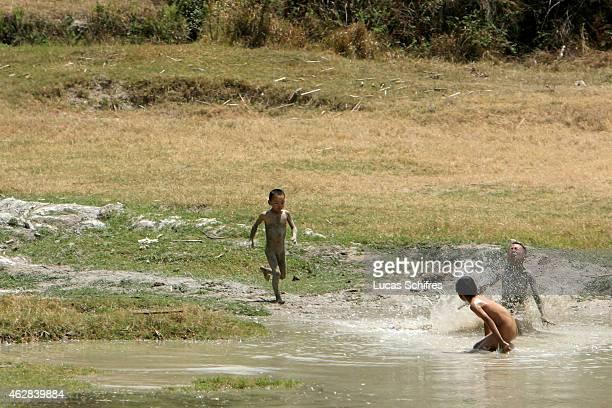 Boys play in the mud on May 3 2007 near Lijiang Yunnan province China