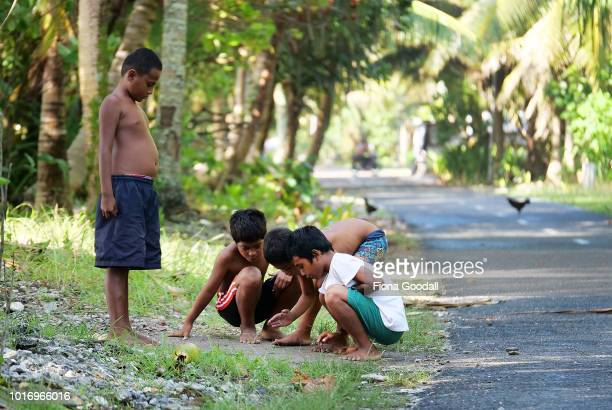 Boys play marbles on the roadside after school on August 15 2018 in Funafuti Tuvalu There are two primary schools on the main island of Funafuti and...