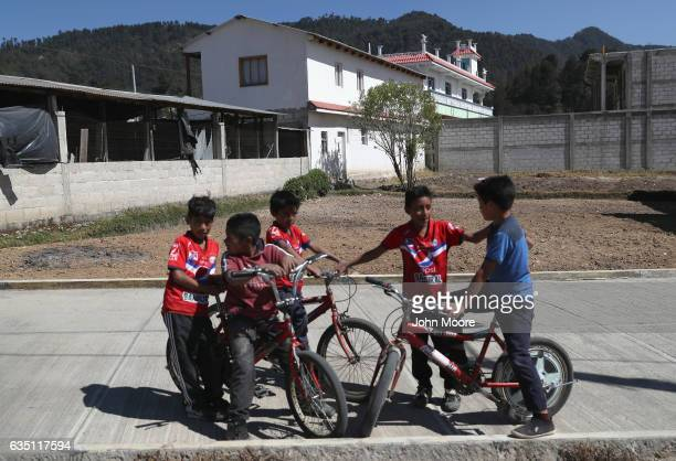 Boys play near a home built with remittance money sent back from the US to Guatemala on February 11 2017 in the western highlands town of Cajola...