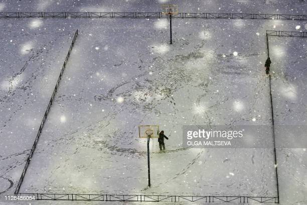 TOPSHOT Boys play on a sports ground during a snowfall under the rays of the sun in Saint Petersburg on March 3 2019