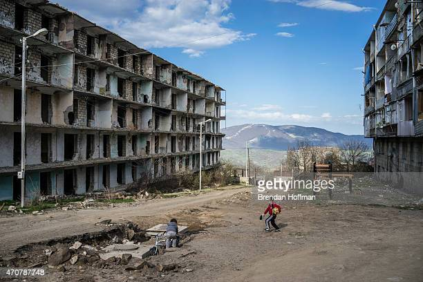 Boys play on a street next to a building destroyed by war more than twenty years earlier on April 18, 2015 in Shushi, Nagorno-Karabakh. Since signing...