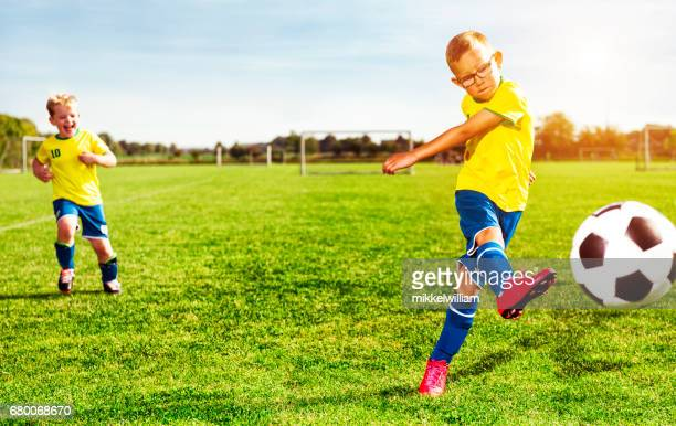 boys play soccer and one player kicks the football - taking a shot sport stock photos and pictures