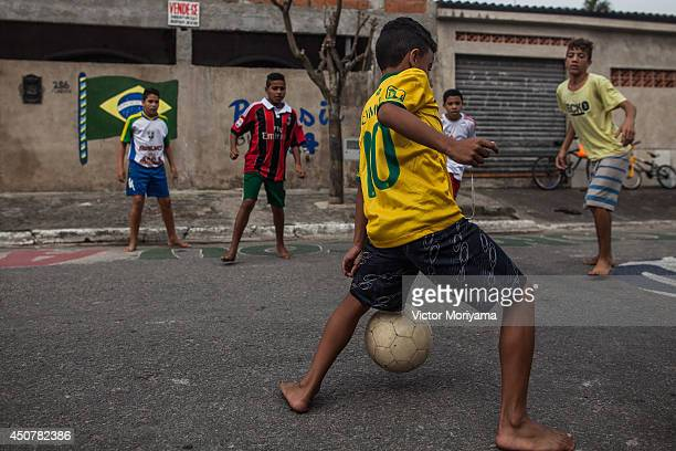 Boys play soccer in the streets of the Garden Gloria neighborhood on June 17 2014 in Praia Grande Brazil Soccer star Neymar of Brazil lived in this...