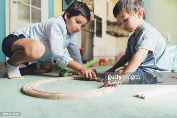 jungen spielen mit holzeisenbahn - nur kinder stock-fotos und bilder