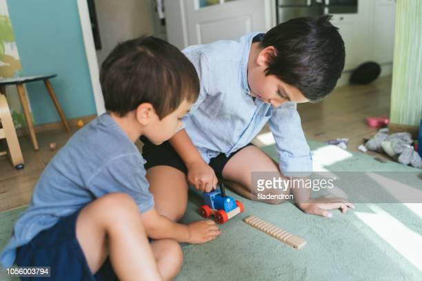 boys play wiht wooden train - innocence stock pictures, royalty-free photos & images