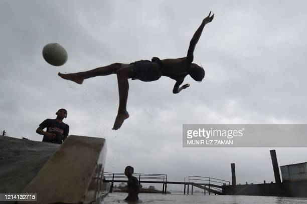 TOPSHOT Boys play with a ball on a river ahead of the expected landfall of cyclone Amphan in Khulna on May 20 2020 Several million people were taking...