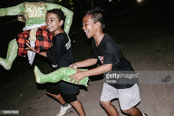 Boys play with a destroyed Ogoh-ogoh after the parade on March 11, 2013 in Tunjuk Village, Tabanan, Bali, Indonesia. For the Balinese, Ogoh-ogohs...