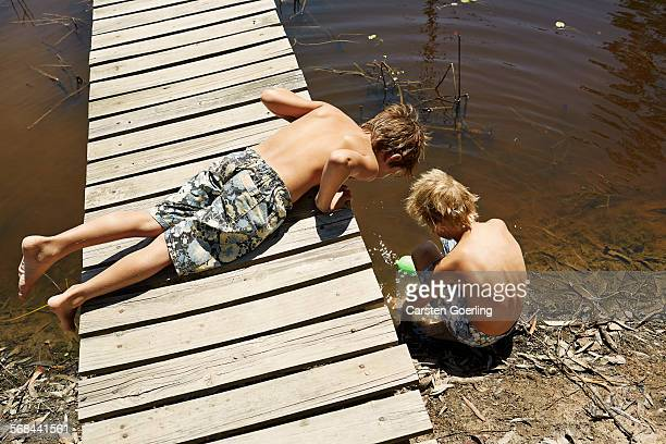 2 boys playing at a jetty