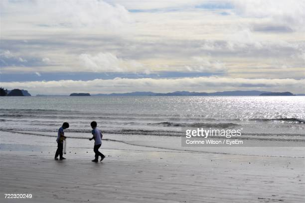 boys playing at beach against cloudy sky - corinne paradis photos et images de collection