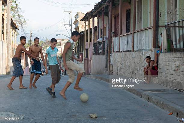 Boys playing bare foot football in the street