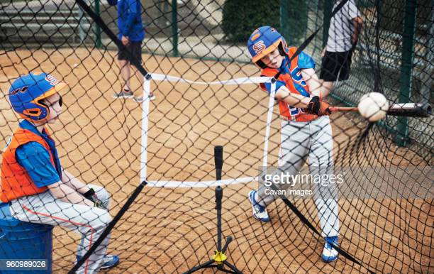 boys playing baseball on field - batting sports activity stock photos and pictures