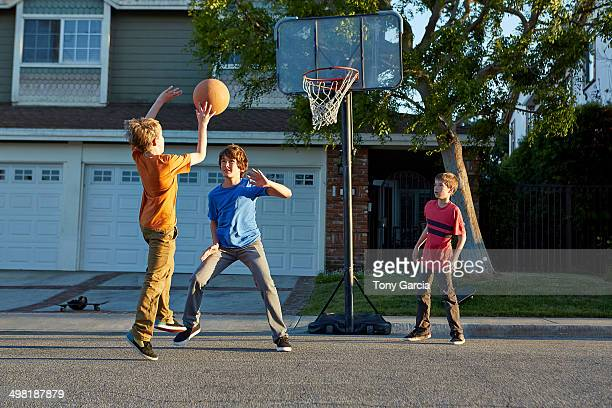 Boys playing basketball outside house
