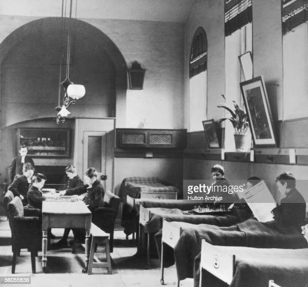 Boys playing chess or reading in a dormitory at Christ's Hospital public school in London circa 1850