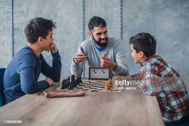 boys playing chess while teacher helping them - chess stock pictures, royalty-free photos & images