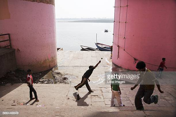 Boys playing cricket beside the Ganges river