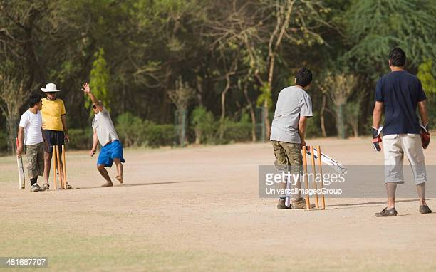 Boys playing cricket in a playground New Delhi India