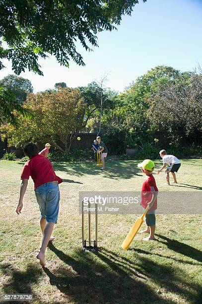 boys playing cricket in backyard - sport of cricket stock pictures, royalty-free photos & images