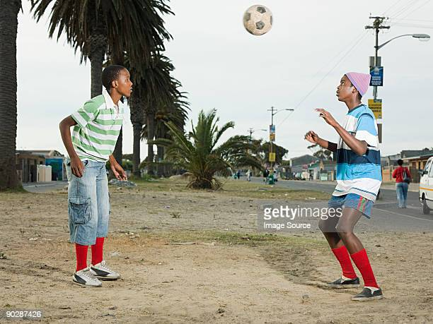 Boys playing football in street