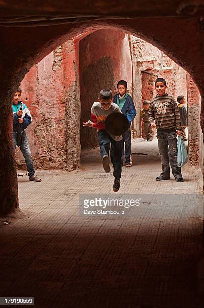 CONTENT] boys playing football in the ancient medina in Marrakech Morocco