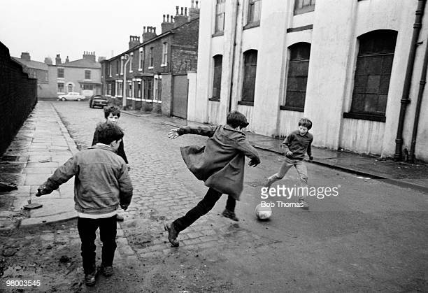 Boys playing football in the backstreets of Manchester circa 1970