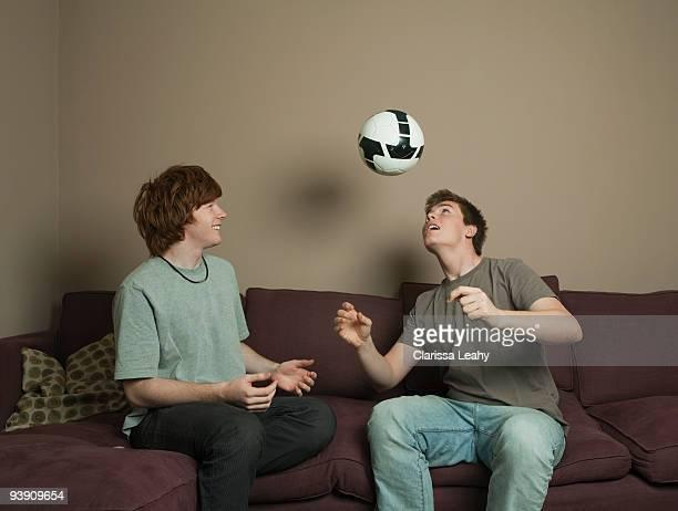 Boys playing football indoors