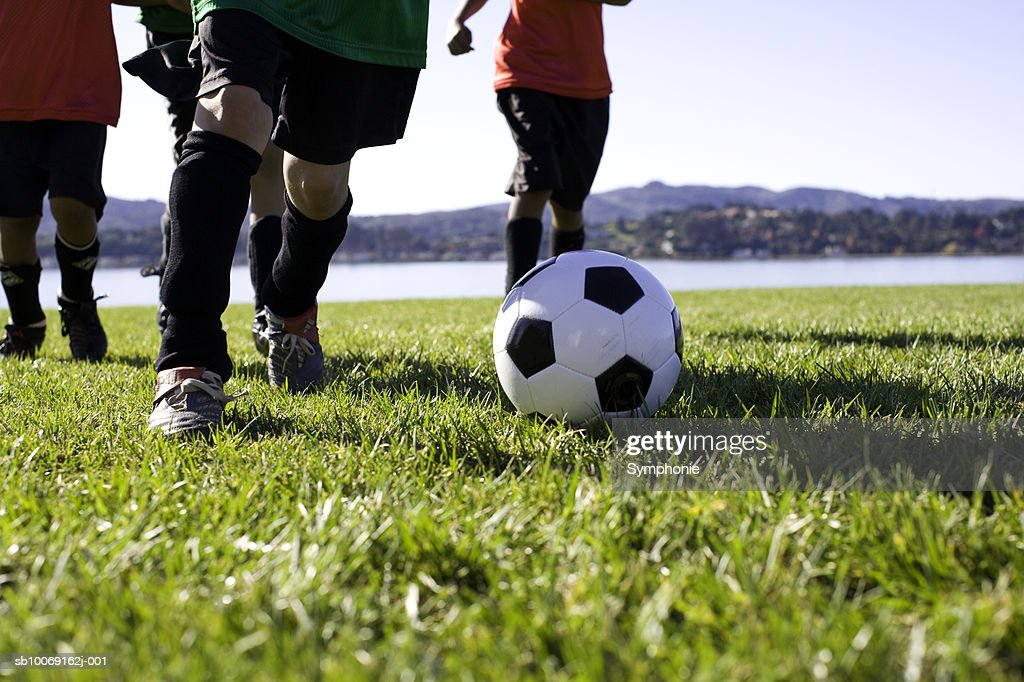 Boys playing football, low section : Stockfoto