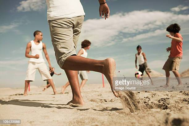 boys playing football on beach - low angle view stock pictures, royalty-free photos & images