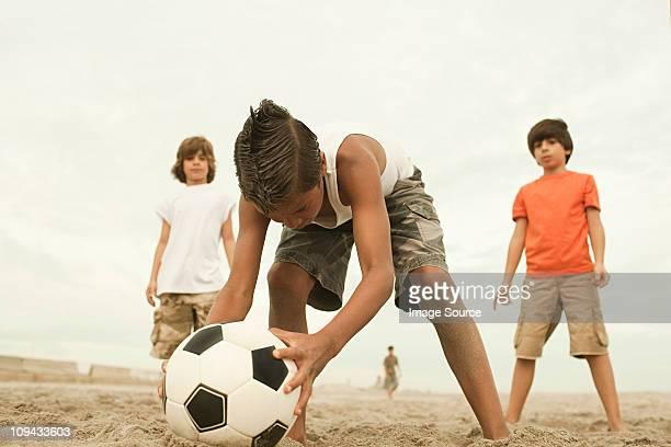 Boys playing football on beach