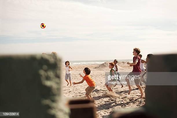 Niños jugando al fútbol en playa, vista a través de la pared