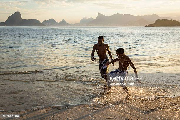 Boys playing football on Niteroi beach with a view of the Guanabara bay Christ the Reedemer statue and the Sugar Loaf mountain Rio de Janeiro