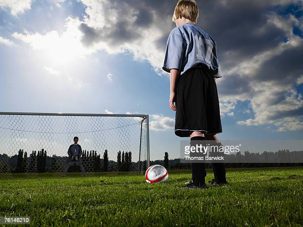 boys (10-11, 12-13) playing football on pitch, rear view, low angle - shootout stock pictures, royalty-free photos & images
