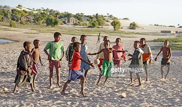 garçons jouant au football sur la plage: anakao, madagascar - madagascar enfant photos et images de collection