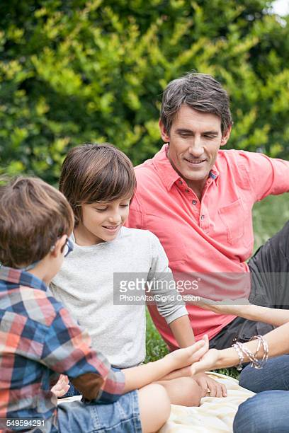 Boys playing hand game with family
