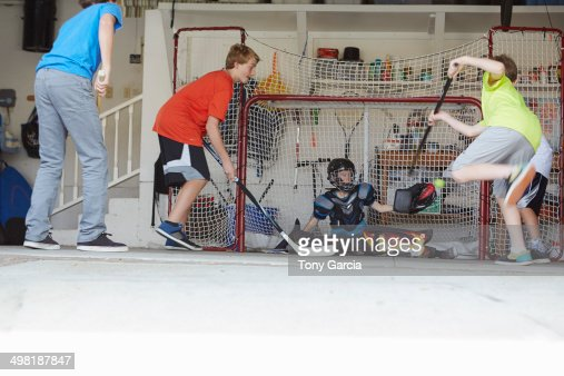 Boys playing hockey in garage