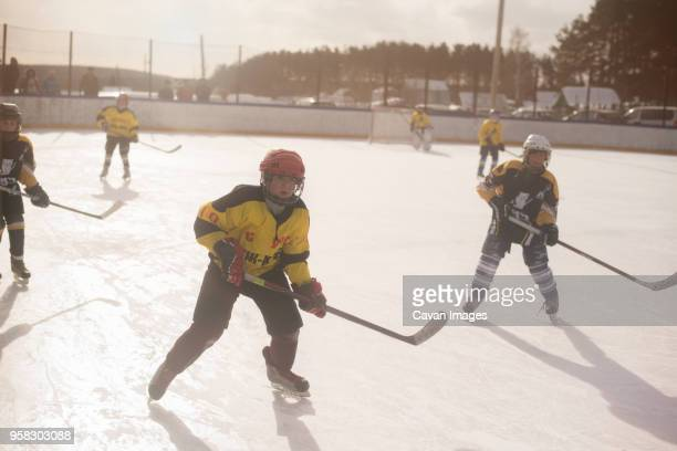boys playing ice hockey on sunny day - ice hockey rink stock pictures, royalty-free photos & images