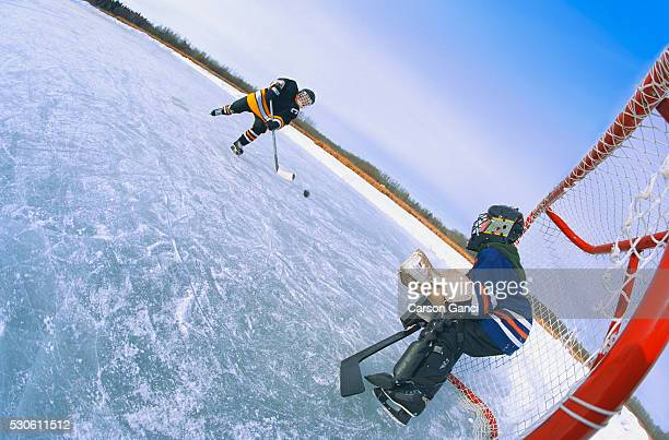 boys playing ice hockey outdoors - ice hockey uniform stock pictures, royalty-free photos & images