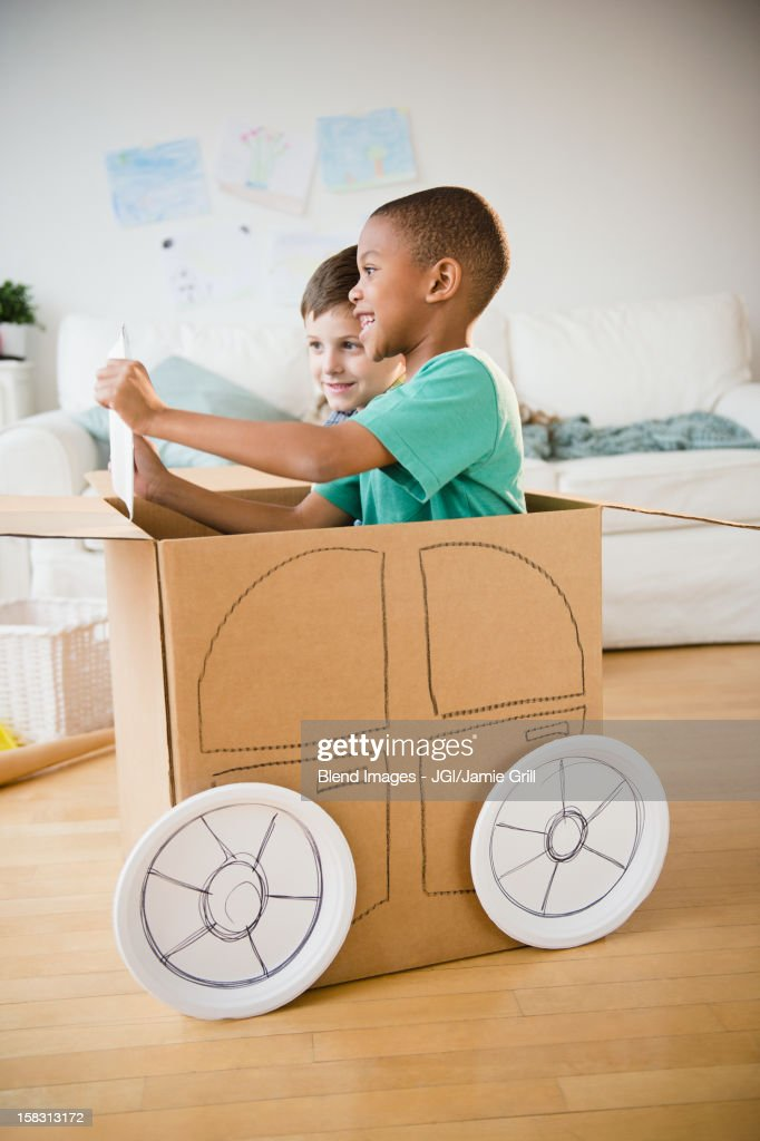 Boys playing in a cardboard car together : Stock Photo