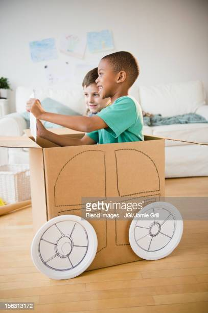 Boys playing in a cardboard car together