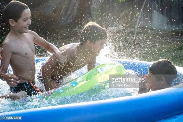 boys playing in swimming pool - google stock pictures, royalty-free photos & images