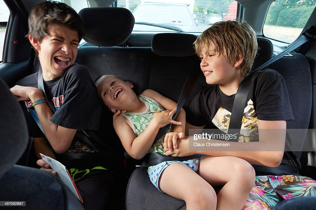 3 boys playing in the back seat of a car : Stock Photo