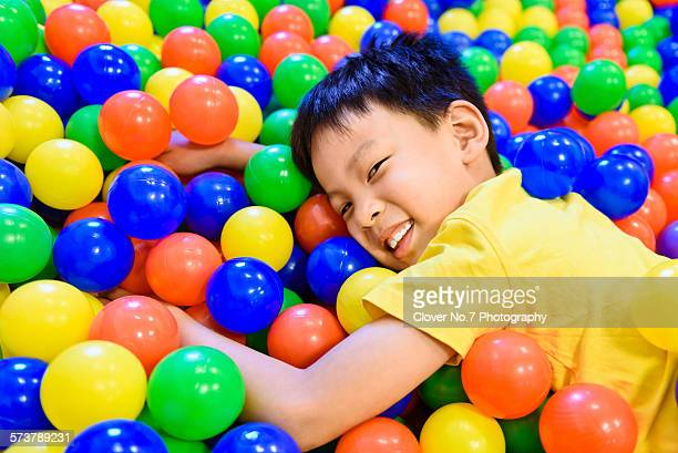 Boys playing in the ball pit.