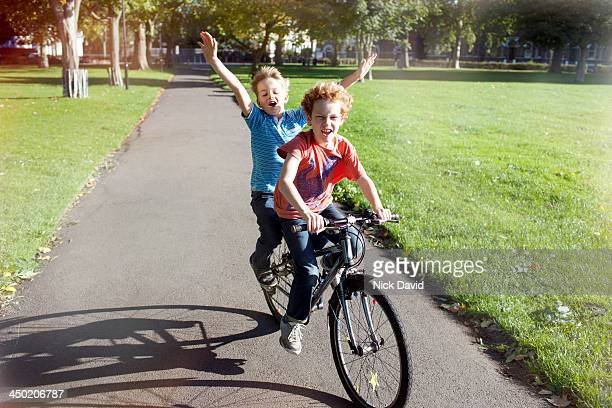 boys playing in the park - hands free cycling stock pictures, royalty-free photos & images