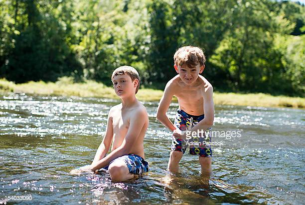 2 boys playing in the river