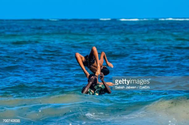 boys playing in the sea - mombasa stock photos and pictures